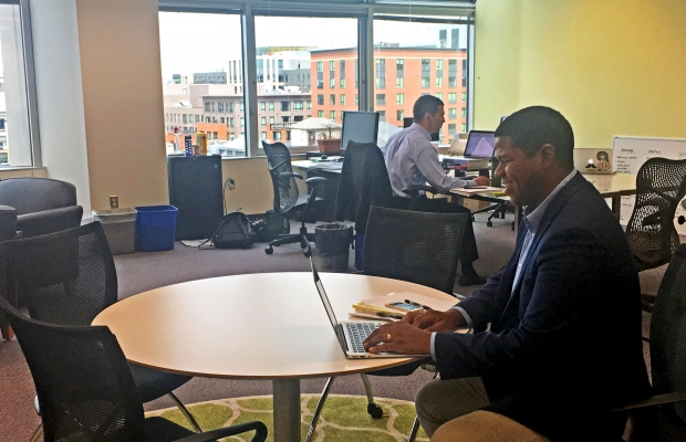 Matthew Henry, Data Resource Specialist at Exceptional Lives, works at a shared table in SIF's Coworking Space